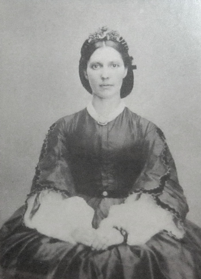 Black and white photograph of young woman in dark dress with arms folded in her lap, hair tied in a bun beneath.