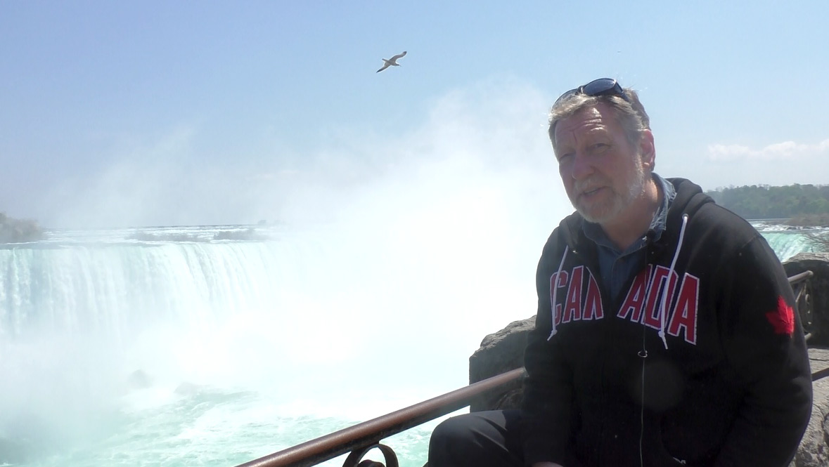 Man with beard and dark blue sweatshirt with 'Canada' inscribed in red faces camera at railing of Niagara Falls.
