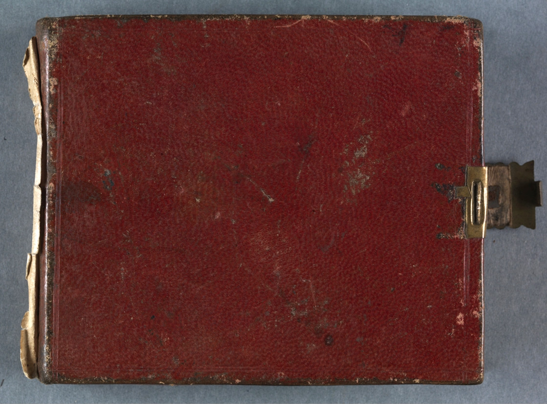 Photograph of red leather bound journal with gold coloured clasp, frayed at bottom.