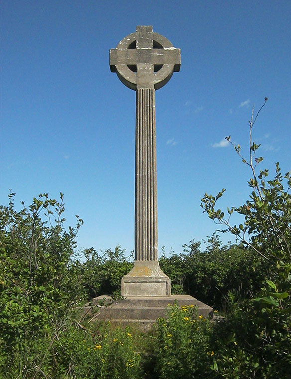Tall grey Celtic Cross with blue sky in background, lush vegetation at its base.