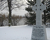 Grey Celtic Cross viewed diagonally in snowy ground, beside river. Inscribed on its base: The Great Irish Famine. 1845-1848, with additional smaller inscriptions underneath.