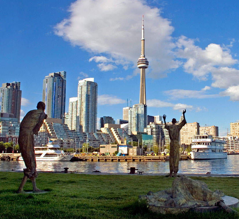 Wide angle image with one sculptural figure lying down in foreground, three standing sculptural figures in middle ground, and city skyline and CN Tower in background across an expanse of water, under a blue sky with white clouds.
