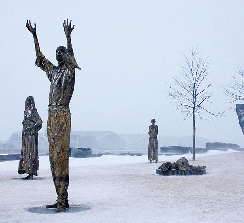 Wide angle image with five sculptural figures, sculpture of man standing with arms upraised in foreground with pregnant woman clutching her stomach to his left, dying woman lying down behind him to his right. Sculpture of man hunched over further right, and sculpture of a boy clutching his hands to his chest in middle ground left. Winter scene with snow on ground, several trees with no leaves, and sculptural wall in background.