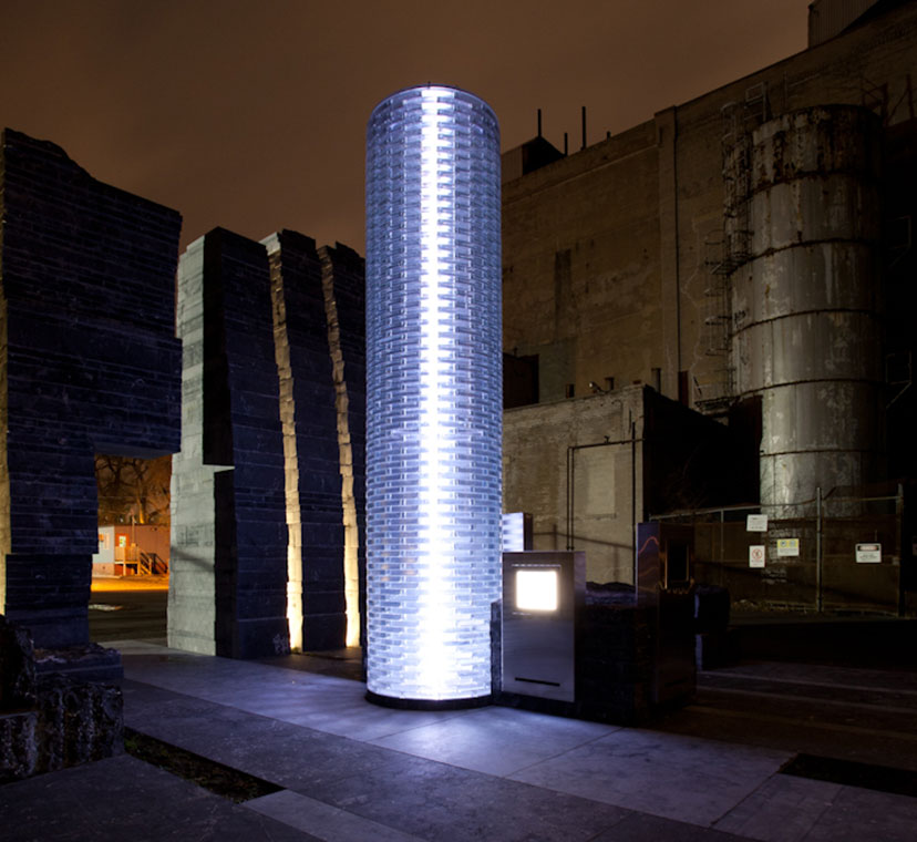 Beacon of light single column of glass lit up at night, surrounded by sculptural stone wall in background. Stone floor stone slab tiles in foreground.