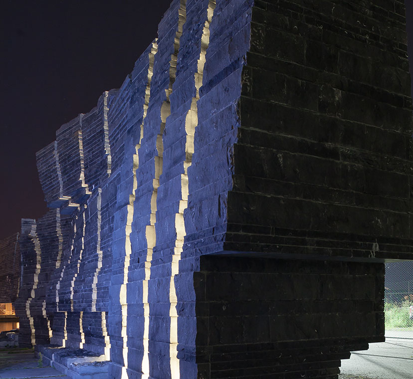 Diagonal view of sculptural stone wall lit up at night, with stone slabs underneath.