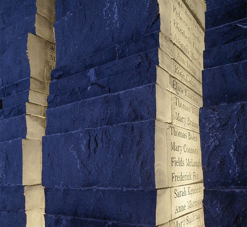Irregular shaped stone column with names engraved on right diagonal side, backlit at night.